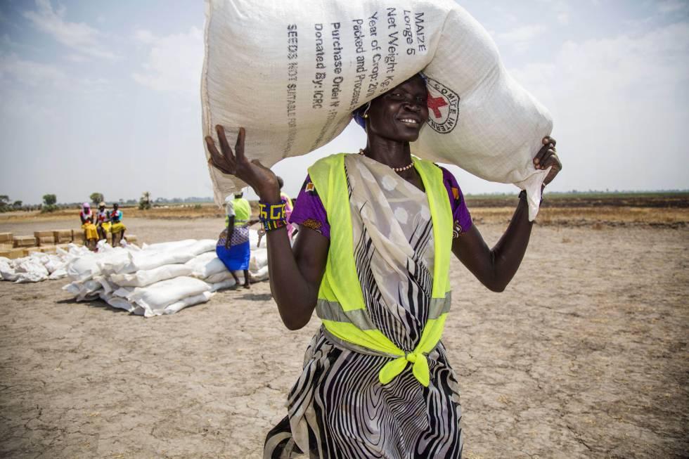 Una voluntaria traslada un saco de semillas en un campo de refugiados en Uganda.