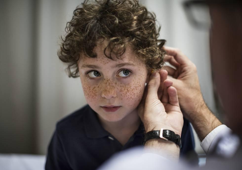 Un médico pone un audífono a un niño.