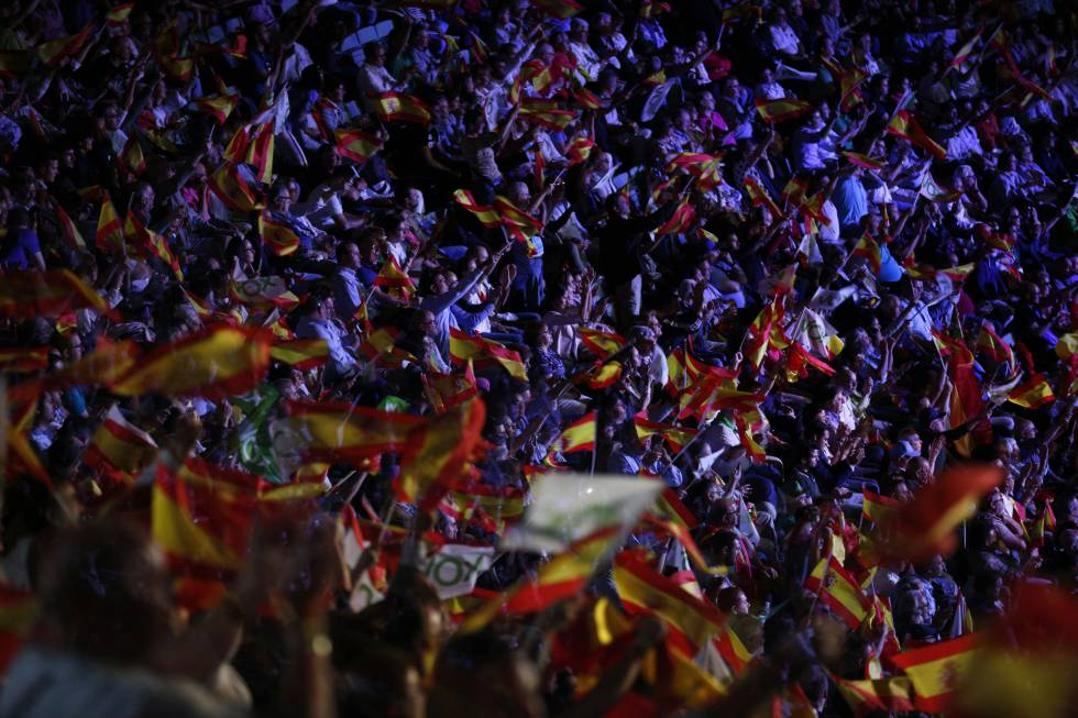 People wave Spanish flags during a Vox rally in Madrid.