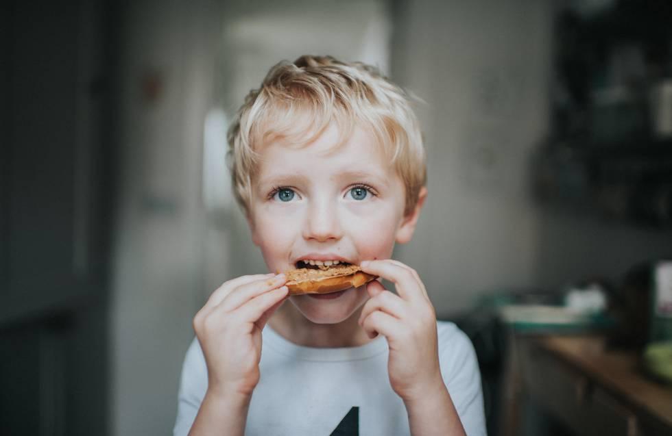 Un niño come una tostada con crema de cacahuete.