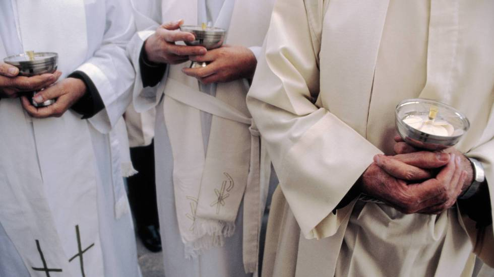 Sacerdotes con cálices durante una misa.