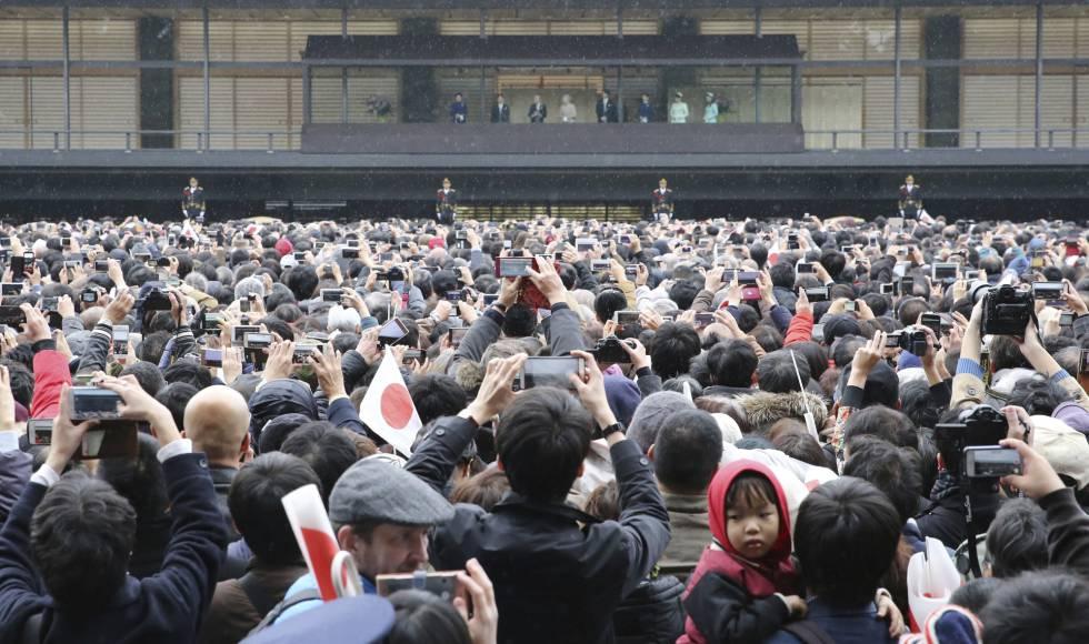 Miles de personas fotografían a la familia imperial japonesa, hoy en Tokio durante la celebración del cumpleaños del emperador Akihito.