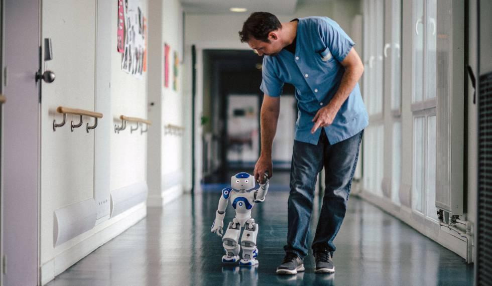 Mickaël Feret, um dos enfermeiros de Jouarre, caminha com o robô pelo hospital.