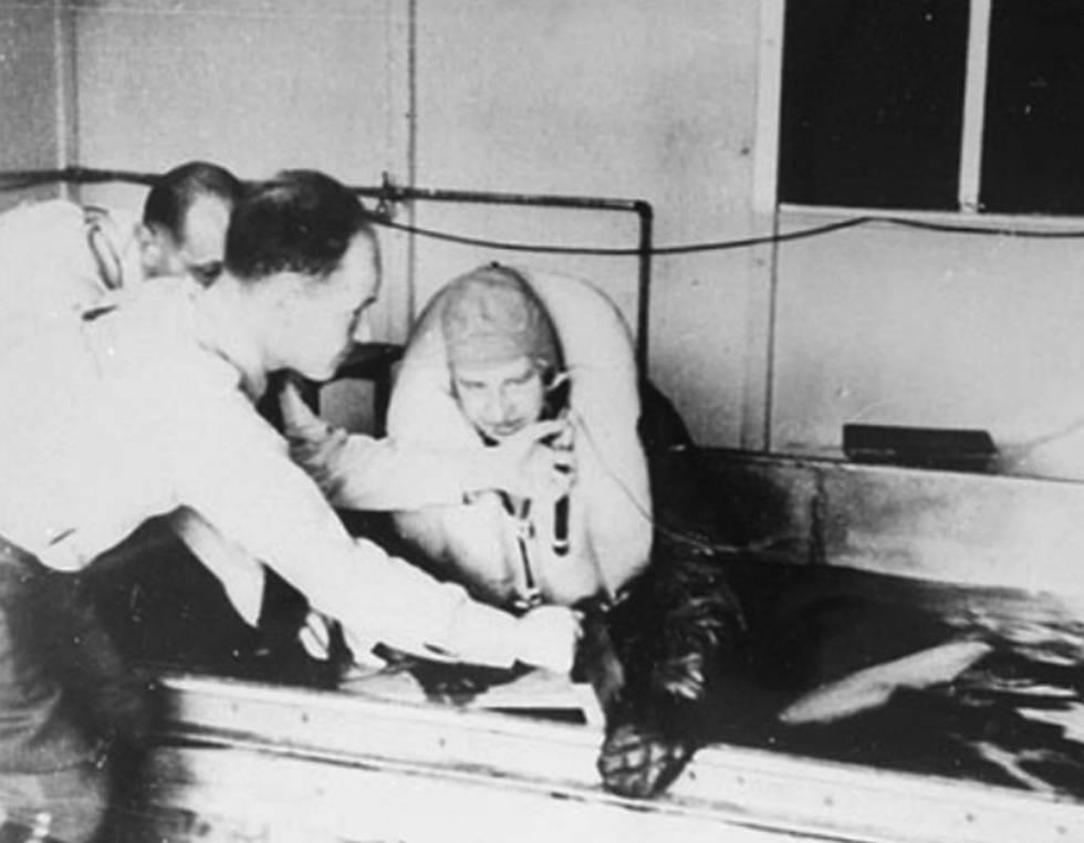 Sigmund Rascher ayuda a un prisionero a sumergirse en agua helada.