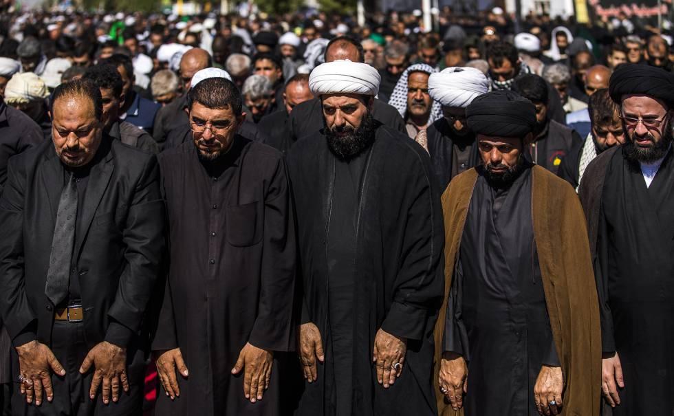Un grupo de clérigos y dirigentes chiíes rezan en el camino a Nayaf. Los chiíes oran con los brazos extendidos y los suníes con los brazos cruzados.