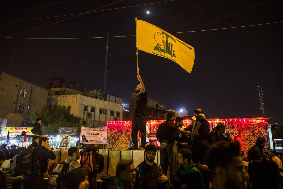 En la madrugada de Kerbala, un militante de Hezbolá ondea una bandera de guerra de la organización libanesa.
