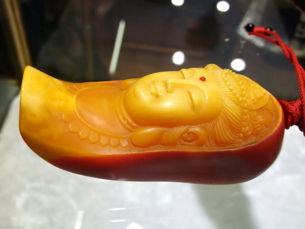 Investigaciones sobre el terreno de organizaciones como TRAFFIC han demostrado la conexión china con el tráfico ilegal del marfil rojo. En la imagen, un colgante de Buda hecho sobre el yelmo de un cálao.