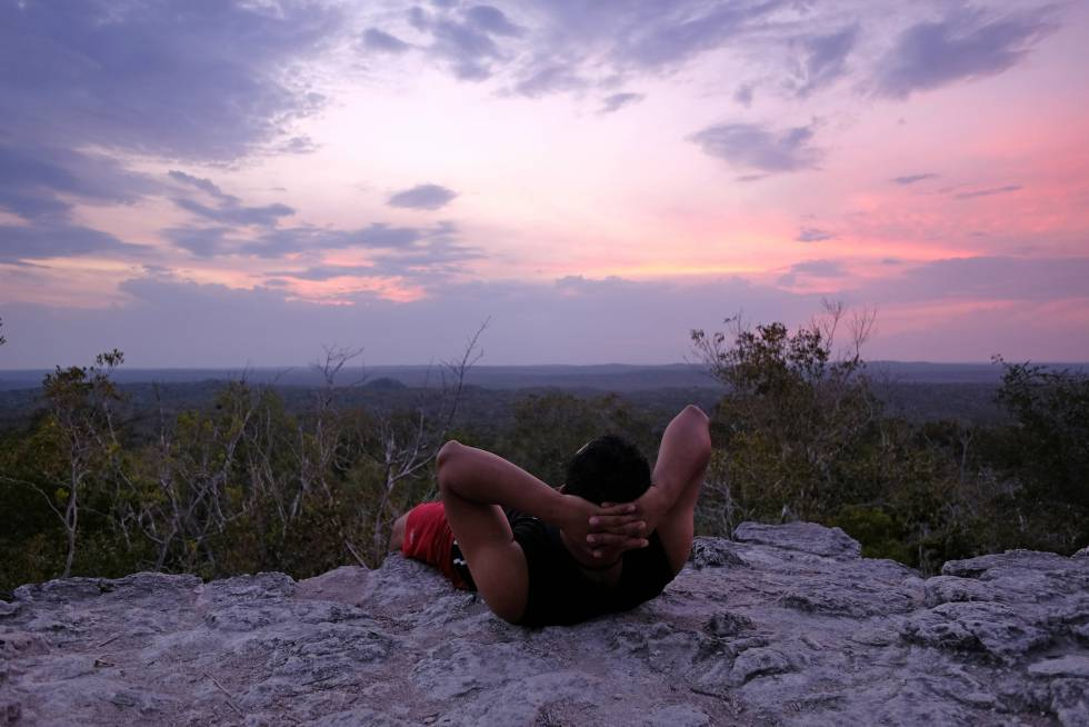 Un turista contempla la puesta de sol desde de la pirámide La Danta, de 72 metros de altura, en las ruinas de El Mirador (Guatemala).
