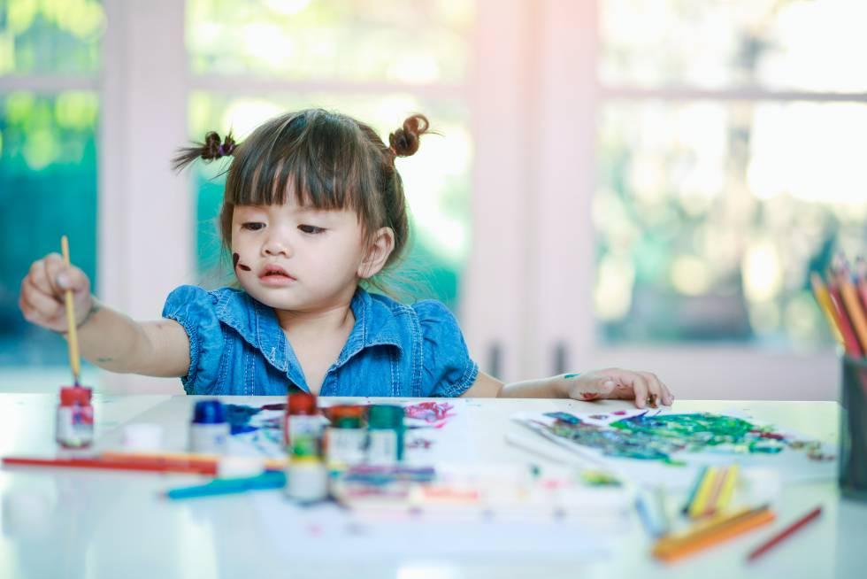 Una niña pinta en casa.