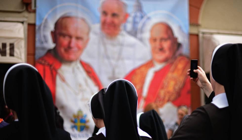 Varias monjas observan y fotografían un panel con la imagen de varios pontífices. rn