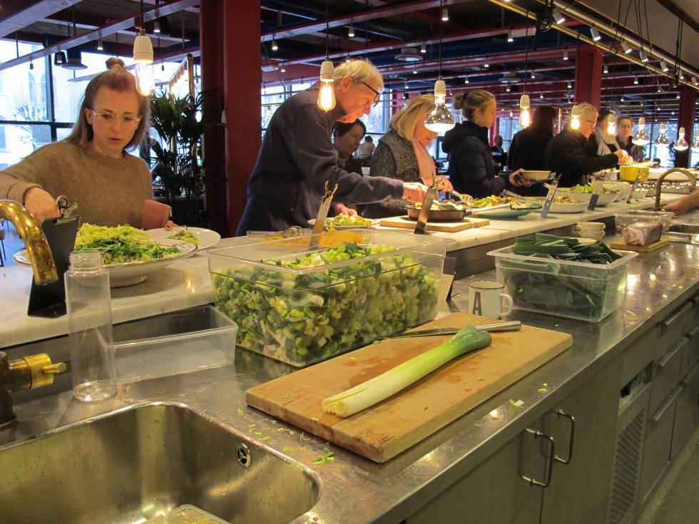 Varios clientes se sirven comida en el restaurante K-märkt.