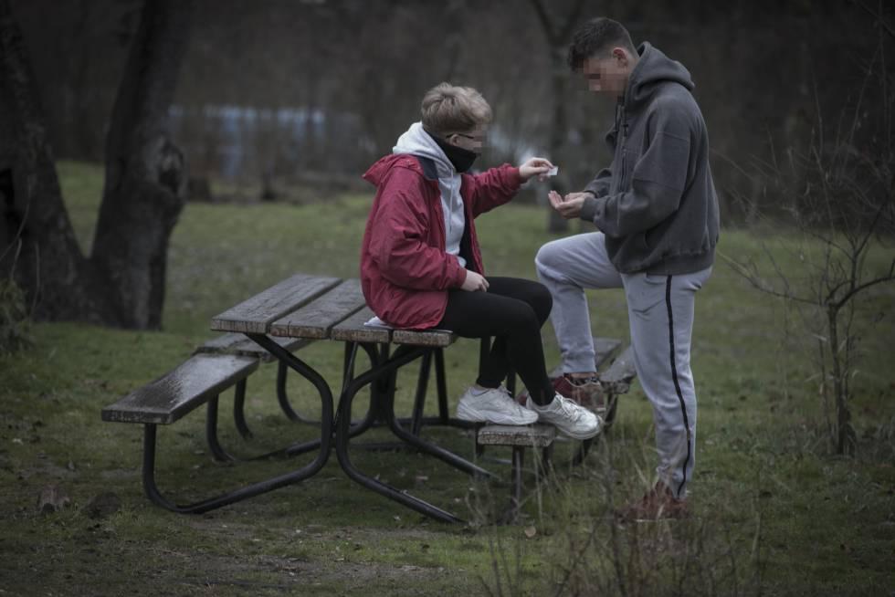 Unos adolescentes preparan un porro en un parque madrileño.