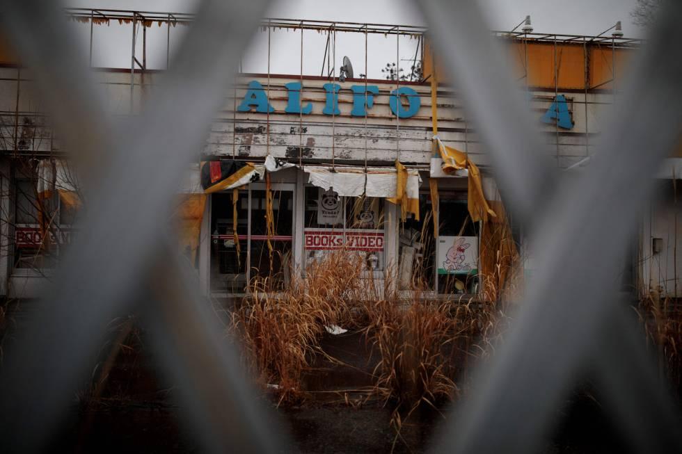 O mato cresce sobre o que parecia ser uma livraria e uma locadora de vídeo em Fukushima.