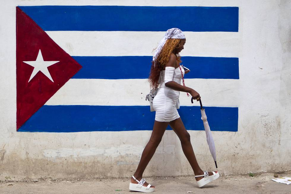 Una mujer vestida de blanco (practicante de la religión yoruba) camina frente a un grafiti de la bandera cubana.