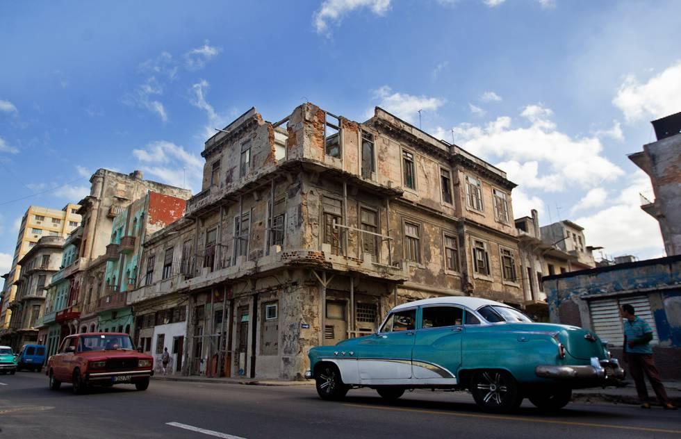 Dos viejos vehículos circulan frente a un edificio semidestruido.