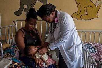 Arriba: El equipo médico del área pediátrica del hospital de Maamobi examina expedientes de enfermos de malaria. Abajo: La doctora Lydia Daytei ausculta a un paciente en el área pediátrica del hospital de Maamobi en Accra, Ghana.