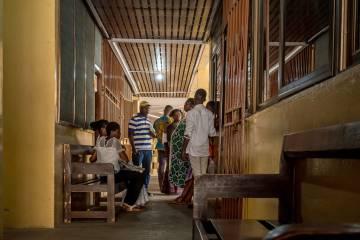 Arriba: Una mujer sale del área ambulatoria del hospital de Maaboni de Accra, donde se ha colgado un cartel advirtiendo del Día Mundial contra la Malaria. Abajo: Pacientes en el hospital de Adabraka, en Accra, esperan a ser atendidos.