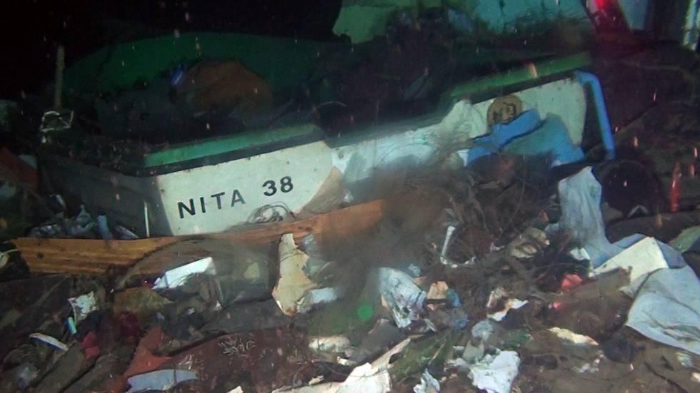 Una embarcación hundida rodeada de basura.