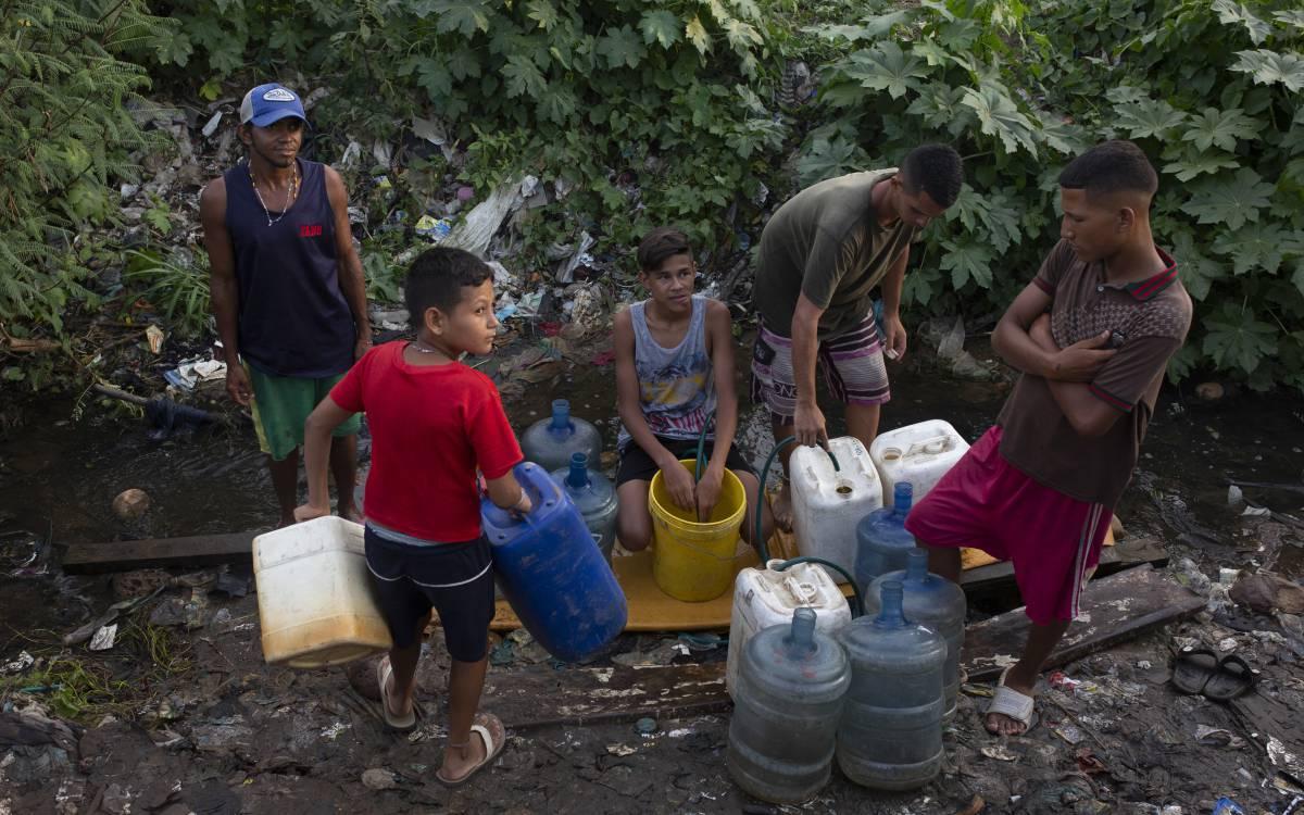 Un grupo de jóvenes se abastece de agua en un riachuelo, en Maracaibo.