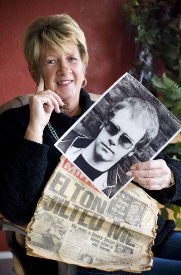 Linda Hannon, ex-namorada de Elton John, com uma foto do cantor quando ainda se chamava Reginald Dwight, e um jornal antigo com sua história.