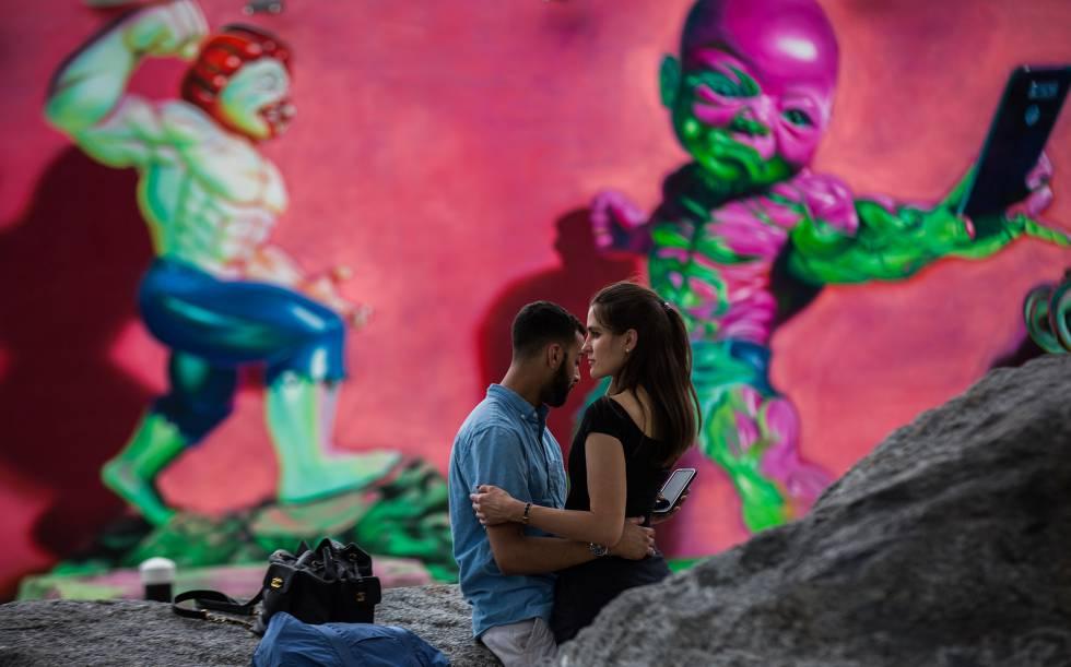 Una pareja, ante un mural en el barrio artístico de Wynwood.
