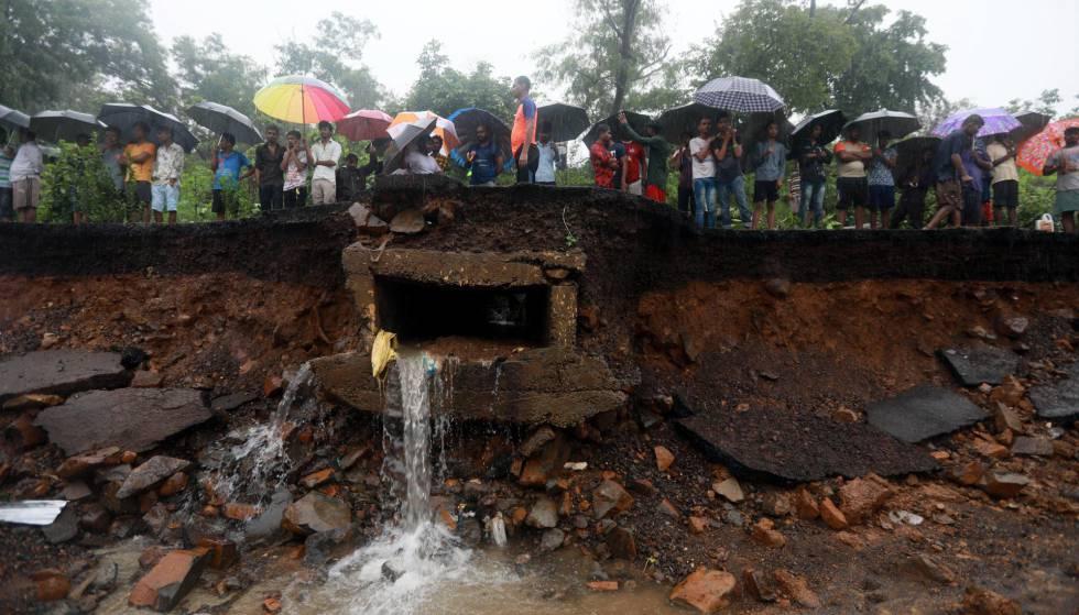 Varias personas permanecen cerca del lugar donde se ha derrumbado un muro en Bombay (India), este martes. Al menos 15 personas han muerto.