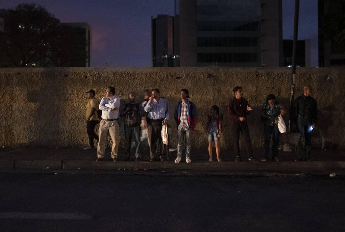 Un grupo de personas espera un autobús en Caracas.