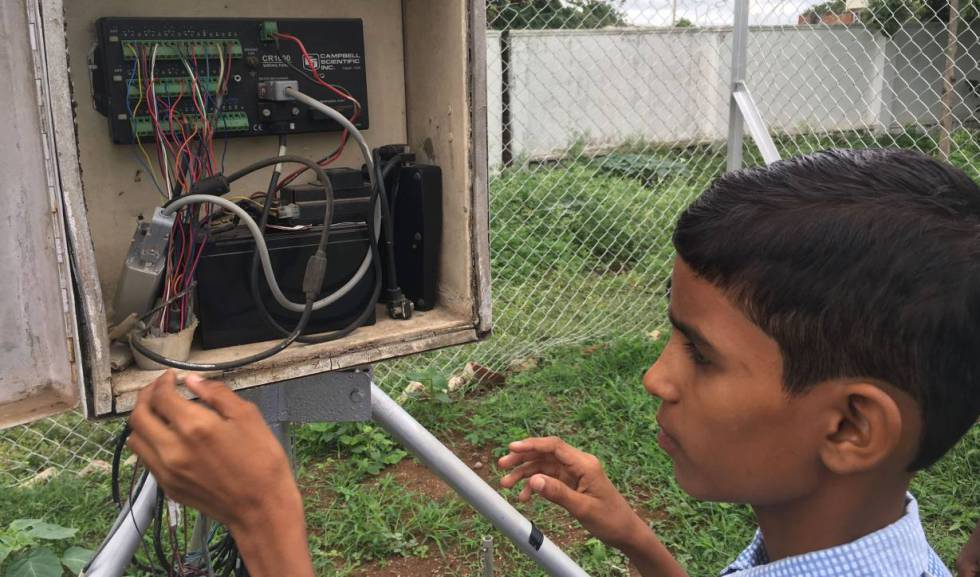 El estudiante Vamshi Voggu revisa la estación meteorológica instalada en el colegio de Kothapalli, India.