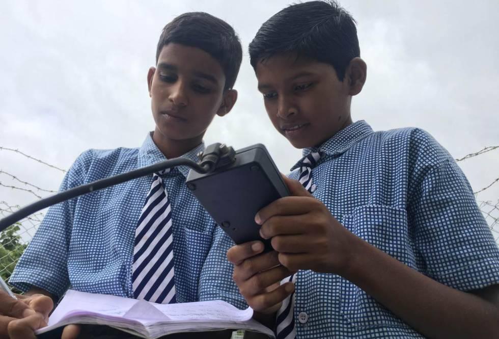 Vamshi Voggu y Gurulingam Goud, apuntan los registros de la estación meteorológica instalada en su colegio.