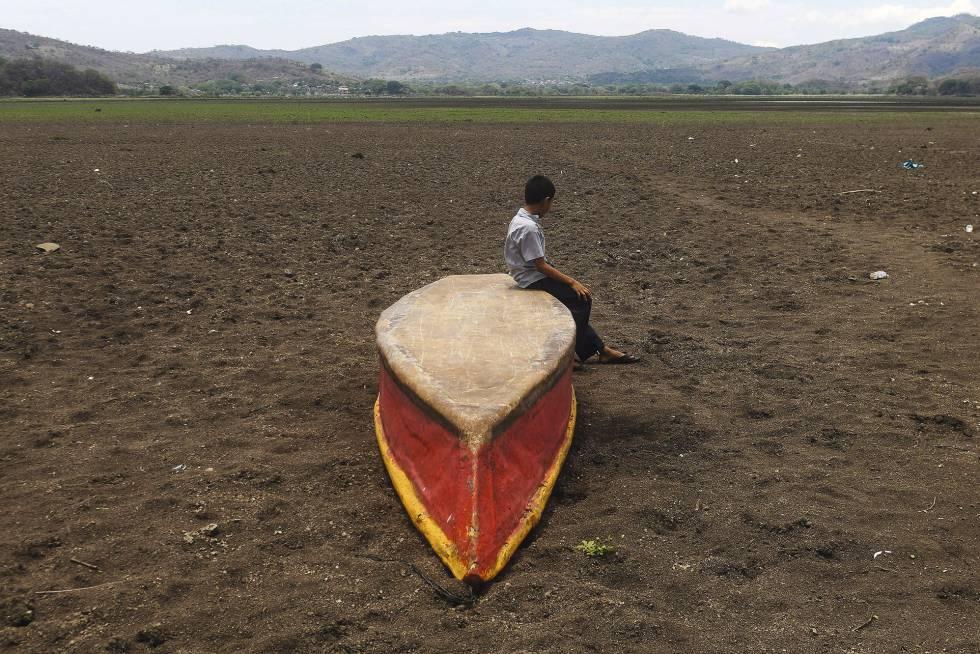 Guatemala.  Um menino sobre um bote no terreno seco que outrora foi o leito do lago Atescatempa.