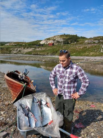 Thomas Hansen, con seis salmones pescados con una red de pesca tradicional, en Noruega.