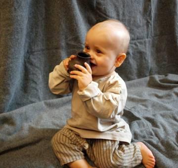 Un bebé prueba una reconstrucción fiel de uno de los biberones prehistóricos.