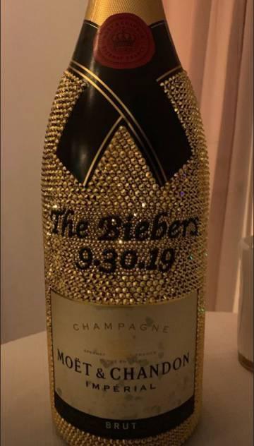Una botella de champán Moet&Chandon cubierta de cristales con el nombre de los novios y la fecha de la boda.
