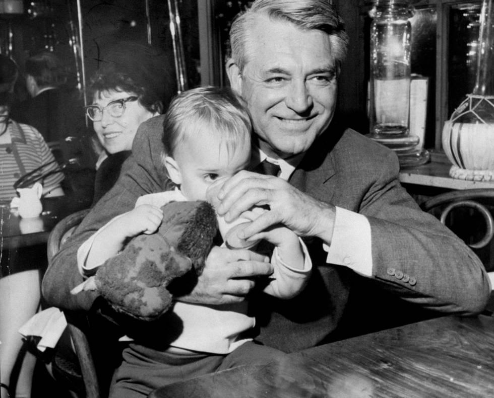 Cary Grant con su hija Jennifer Grant en brazos en un restaurante en 1967.
