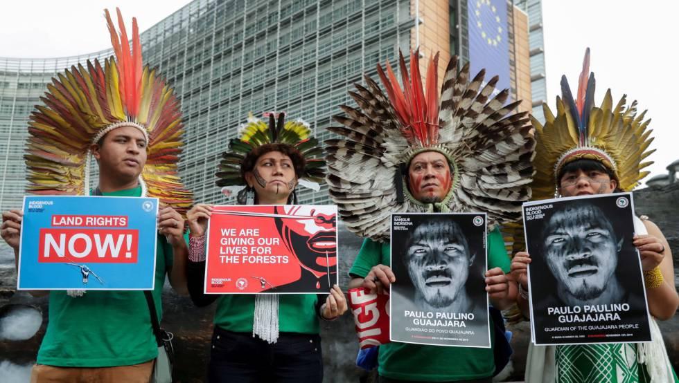 Erisvan Guqjajar, Nara bare, Celia Xacriaba y Kreta Kaingang, líderes indígenas brasileños, posan frente a la sede de la Comisión Europea en Bruselas el pasado 5 de noviembre con carteles que denuncian el reciente asesinato del activista Paulo Paulino Guajajara y el fin de la deforestación de la Amazonia.