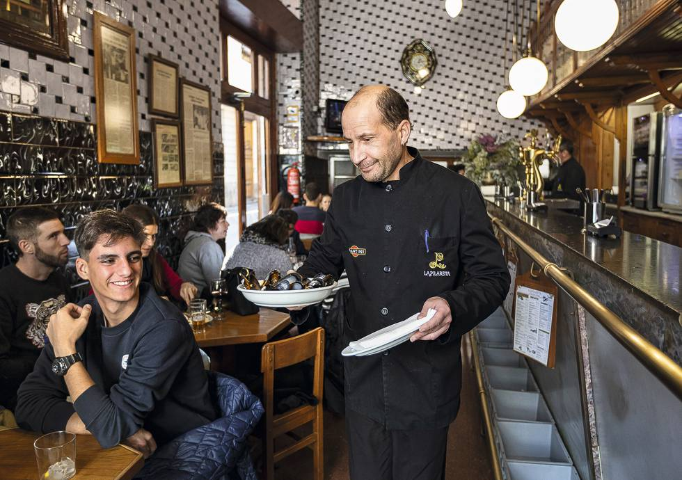Un camarero del bar La Pilareta, en Valencia, sirve una ración de clòtxines.