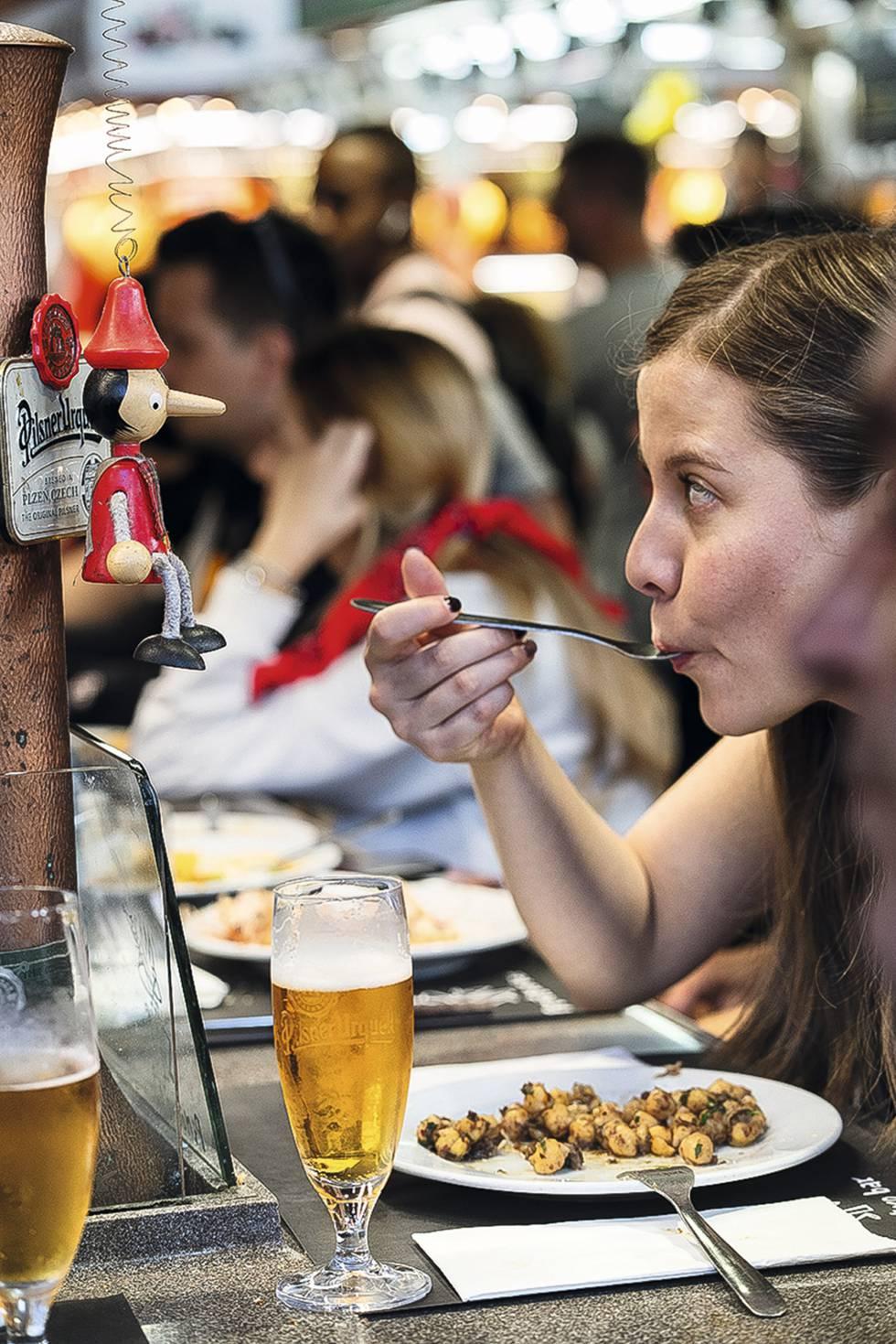 Una clienta come una ración de garbanzos con morcilla en el Pinotxo Bar, en el Mercado de la Boquería de Barcelona.