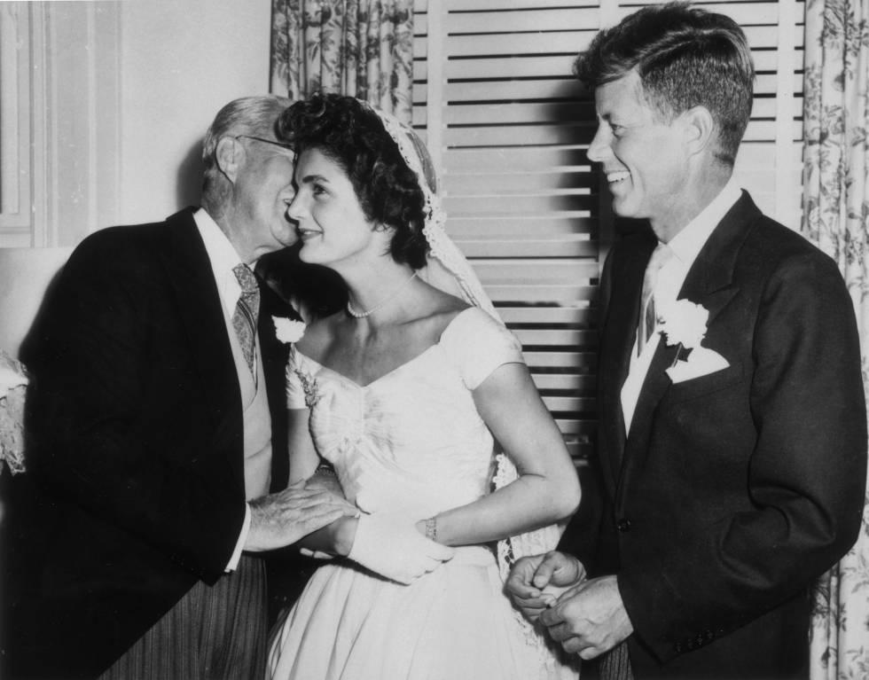 Joseph Kennedy (1888 - 1969) susurra algo al oido de a su nueva nuera Jacqueline Bouvier el día de su boda, mientras su esposo John F. Kennedy mira, sonrient. Fue en Newport, Rhode Island, el 12 de septiembre de 1953.