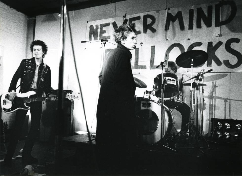 Sid Vicious, Johnny Rotten y Paul Cook, integrantes de los Sex Pistols, en un concierto en 1977. Al fondo, el título de su primer y único disco, 'Never mind the bollocks'.