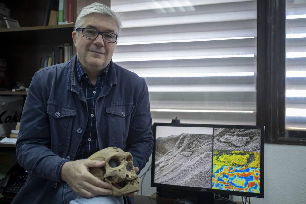 Fernando Muñiz, uno de los investigadores de las huellas de los neandertales, sostiene la reproducción de un cráneo de estos homínidos mientras muestra la huella hallada en Gibraltar.rn