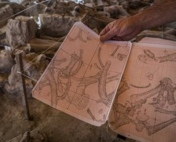 Archaeologist Luis Córdoba shows his drawings of the excavation.