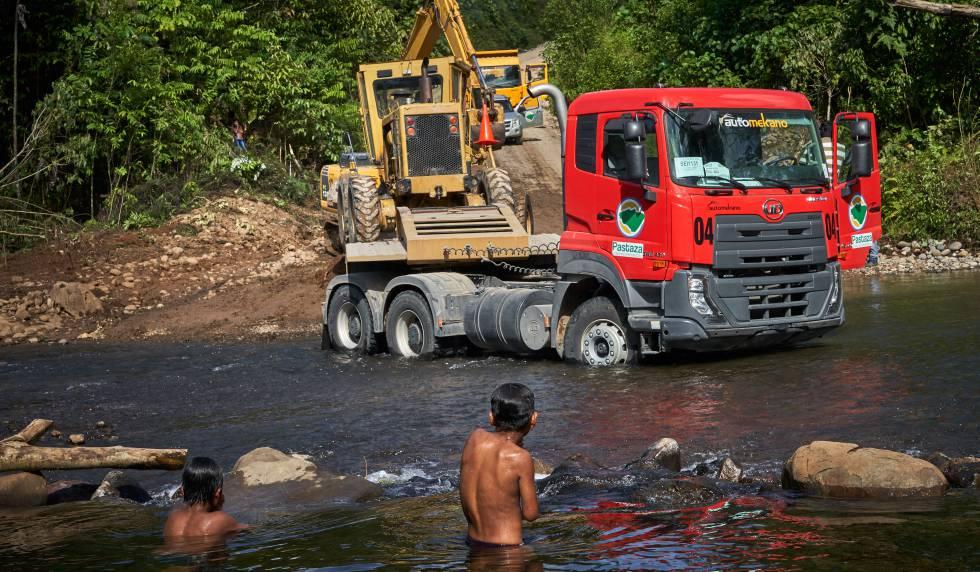 Niños indígenas shuar observan los camiones cargando una excavadora.