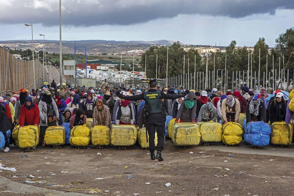 Les porteurs dans le passage de Chinatown à Melilla attendent l'ordre de la garde civile de passer avec les balles au Maroc.