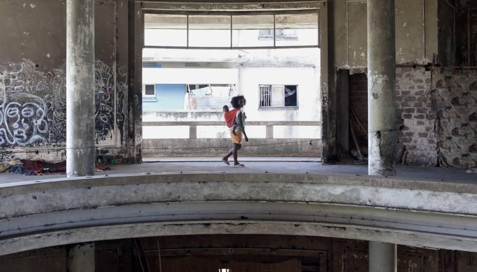 Una mujer camina con su hijo por una de las galerias del hotel.