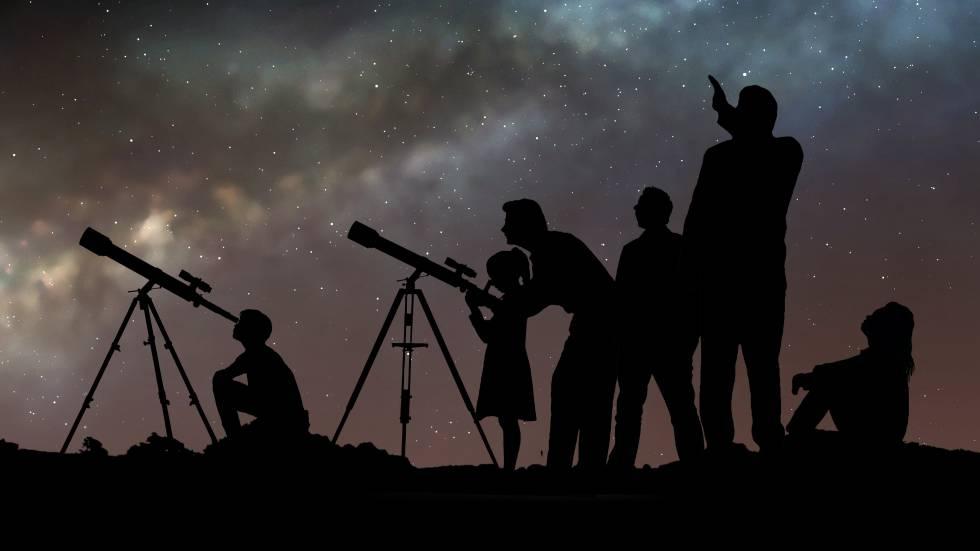 Un grupo de personas mira las estrellas con telescopios.