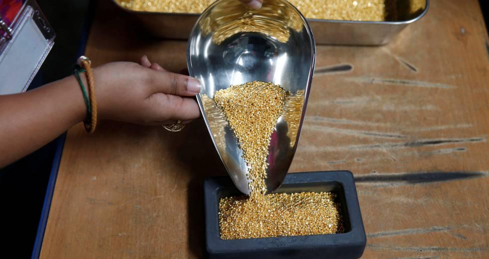Una trabajadora de la refinería ugandesa manipula los granos de oro.
