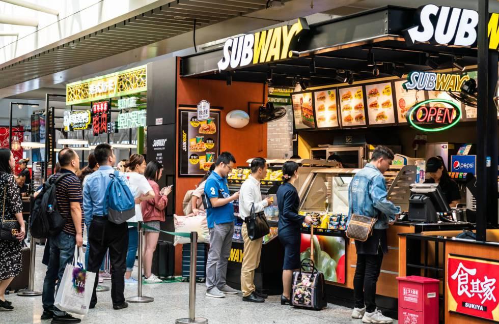 Ciudadanos chinos hacen cola en un restaurante de comida rápida en una estación de tren de Sanghái.