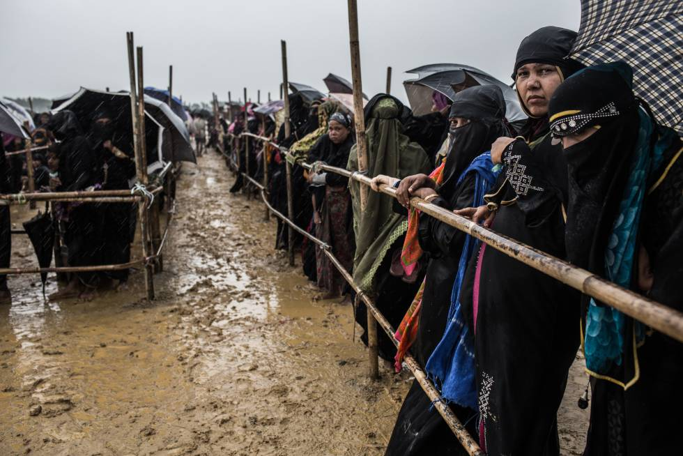 Personas refugiadas rohinyá hacen cola durante horas bajo la lluvia esperando la llegada de ayuda humanitaria.