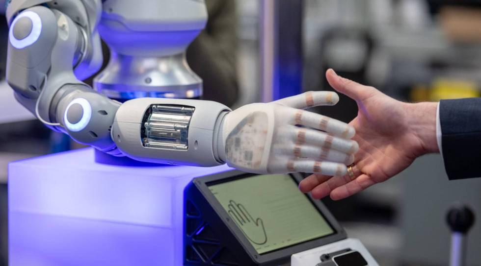 Un hombre tiende la mano a un robot.