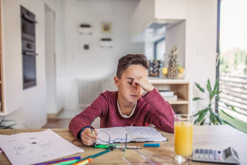 Un niño agotado hace los deberes en casa.